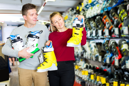Positive family are choosing modern boots for skiing in sport store