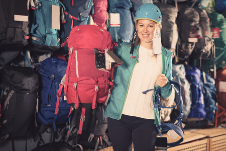 Positive girl chooses good backpack in sporting goods store Stock Photo