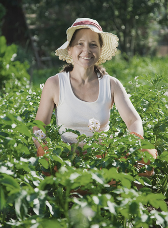 Smiling woman sitting in plant of potato