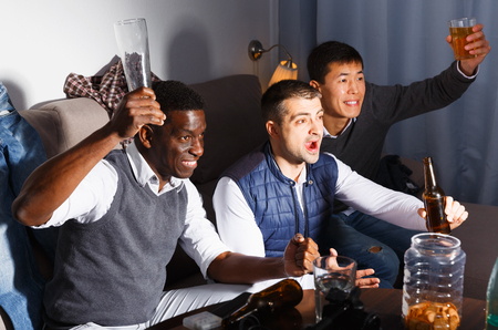 Exalted male friends watching tv together at home, enjoying beer in home interior Фото со стока