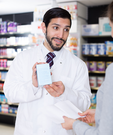 Man pharmacist is recommending medicine for young girl client in apothecary.