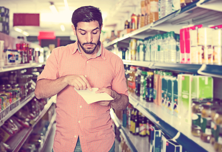 Portrait of  handsome european man customer who is standing with note list in supermarket. Zdjęcie Seryjne