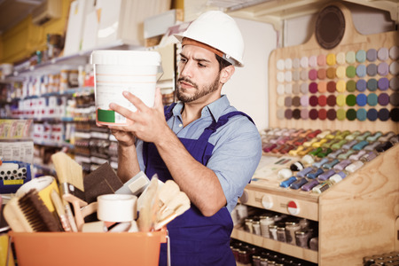 Focused cheerful positive  workman choosing materials for renovation works in paint store Stock Photo