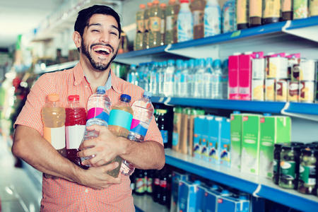 Portrait of smiling american  man customer who is standing with drinks in supermarket. Stok Fotoğraf