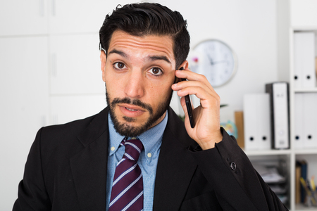 Surprised spanish businessman is talking phone with his partner in office.