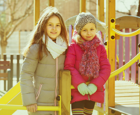 Two positive preschooler age girls at urban playground Standard-Bild