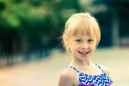 Portrait of cute smiling little girl in summer park