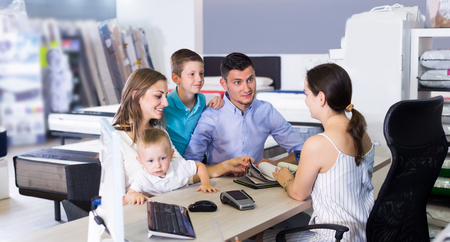 Happy family choosing material for mattress with saleswoman in salon
