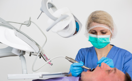 Professional female dentist examining and performing treatment to adult man