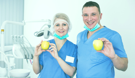 Qualified stomatologists smiling confidently at dental office, showing fresh yellow apples