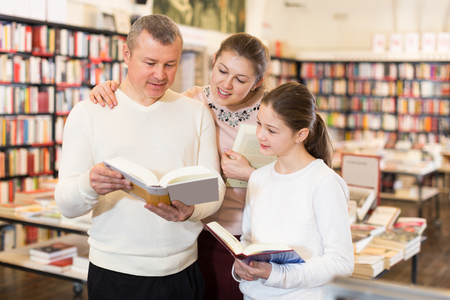 Portrait of happy intelligent family with girl browsing books in library