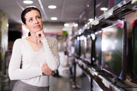 Young woman selecting television set in household appliances store