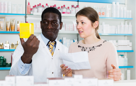 African American man pharmacist discussing prescription medicines with woman customer in drugstore 写真素材