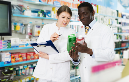 Experienced male and female pharmacists taking inventory of medicines in pharmacy