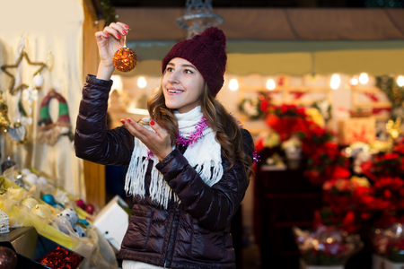 Attractive woman choosing Christmas decoration at market in evening time