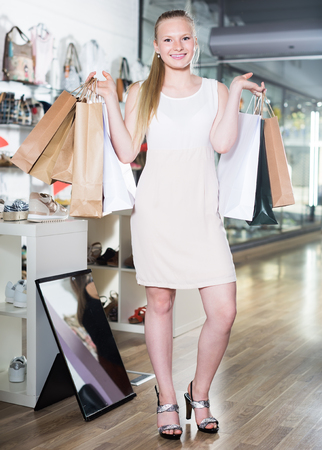 Smiling womanl bragging shopping in a shoe store Stock Photo