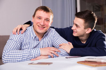 Man with his adult son are posing together at the home.