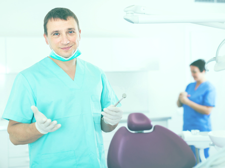 Portrait of adult dentist in medical center standing near the chair