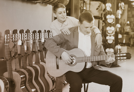 Ordinary teenager and father deciding on acoustic guitar in musical shop