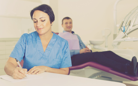 worker dentist professional sitting in medical room with adult patient
