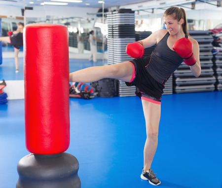 Portrait of young female boxer training with punching bag in box gym