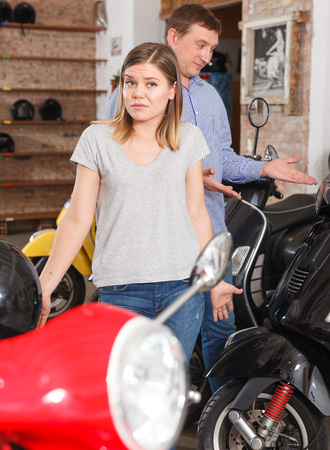 Couple is choosing new motobike and woman is surprised choice her husband in moto store. Stock fotó