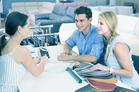Portrait of a couple who are consulting with the assistent about the choice of a color for new sofa