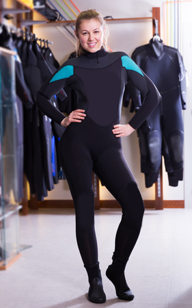 happy young woman is posing in new costume for diving in the store.