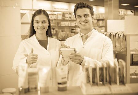 Smiling pharmacist and pharmacy manager posing in drugstore