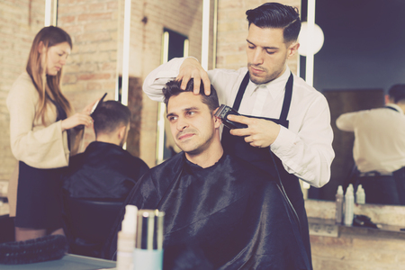 Skillful man barber making hairstyle for male client in hair studio, using electric trimmer