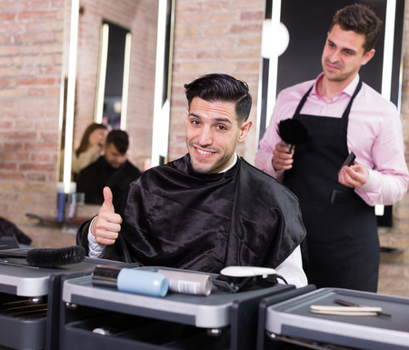 Portrait of delighted male client in salon after haircut from professional hairdresser