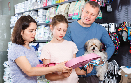 Friendly cheerful  glad family with little dog buying pet supplies in store