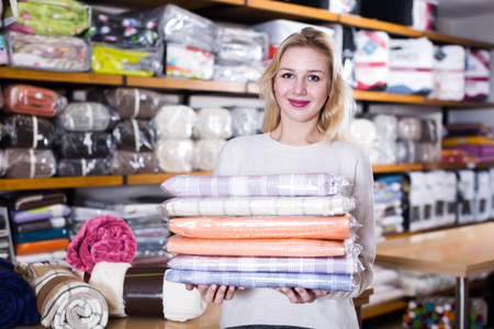 Adult girl customer showing bought home textiles in textile shop Reklamní fotografie