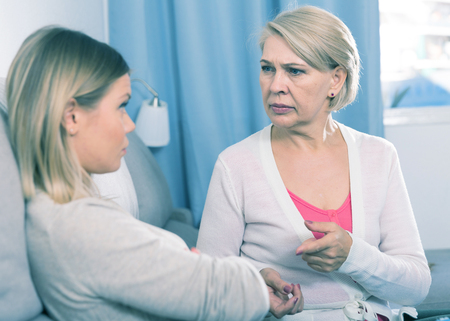 Frustrated middle-aged woman scolds a depressed adult daughter
