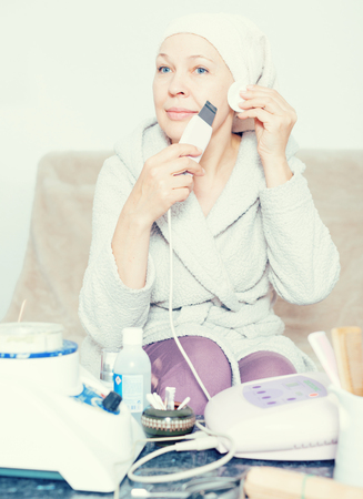 Mature woman getting face cleaned with ultrasonic device at home 版權商用圖片