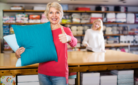 Aged female seller is showing wide assortment of pillows in a textile store.
