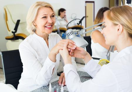 Pretty women doing manicure in nail salon