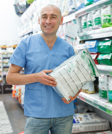 Adult man veterinarian seller with pet dry food standing near shelfs  in pet store