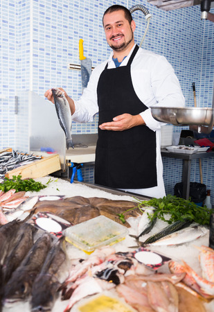 Adult seller in black apron showing fish in hands