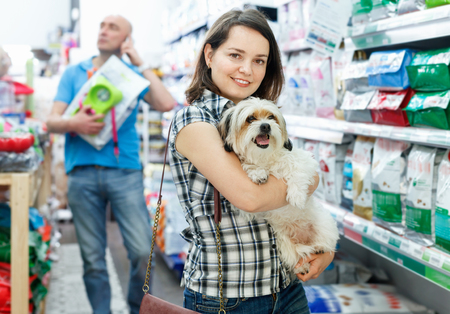 Joven mujer sonriente positiva feliz con perro en la tienda de mascotas, durante las compras con el marido