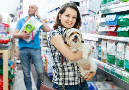 Junge glückliche positiv lächelnde Frau mit Hund in der Tierhandlung, während des Einkaufens mit Ehemann