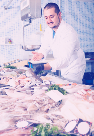 adult seller in white cover-slut holding fish in his hand Stock Photo