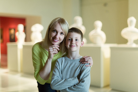 Young american mother and son exploring old statues in museum