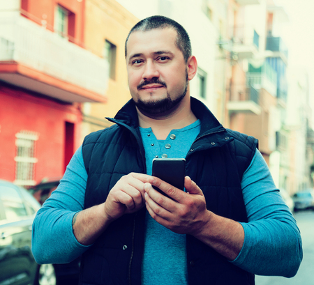 Handsome adult man in blue stands on street with phone