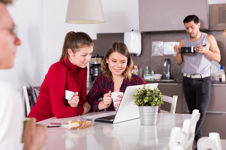 Young female travelers with laptop planning tourist itinerary during breakfast in hostel kitchen