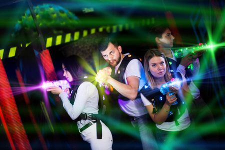Modern young people playing laser tag on dark labyrinth in bright beams of laser pistols