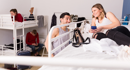 Handsome man talking and flirting with smiling girl who sitting on bunk bed in hostel