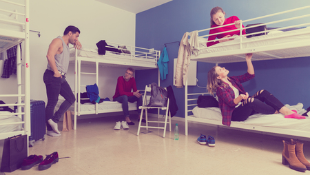 Young tourists staying in cozy hostel, friendly talking to each other