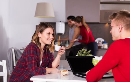 Positive girl sitting in kitchen of hostel with cup of tea, talking to guy with laptop Stock Photo