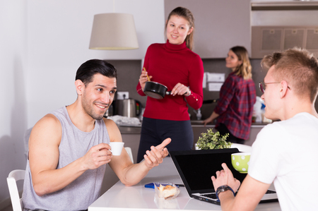 Positive man with cup of coffee talking to guy sitting in kitchen of hostel with laptop Stock Photo